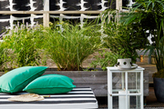 An outdoor cushion with pillows, a hurricane lantern, and an outdoor rug against outdoor curtains and plantings
