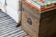 Woven carpet below a rustic chest and cozy sofa.