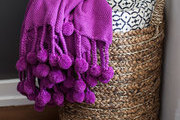 A purple throw with pom pom fringe and a navy printed quilt in a  woven basket
