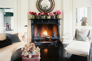 Vases of pink peonies atop a black marble mantel