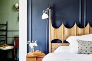 A French-style bedroom with blue walls and a wooden headboard.