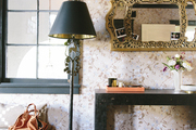A bronze lamp in an entry next to a black console and floral wallpaper
