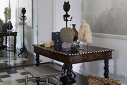 A carved wood table with assorted eclectic objects and sculptures