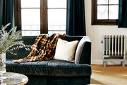 A velvet sofa and pouf in a living room at Palihouse Santa Monica