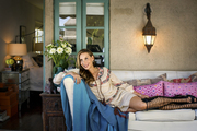 Jacqui Getty lounging on a terrace couch topped with colorful throw pillows