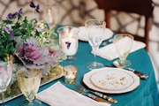 A table set with Limoges porcelain, horn flatware, and a purple-and-green centerpiece