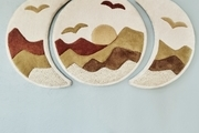 A sunset-inspired wall decor piece that draws attention to the animal stool below it.