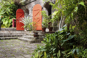 Bright red doors against gray stone and vibrant greenery