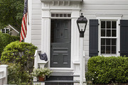A home in Sag Harbor with blue window shutters and a white picket fence