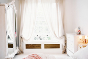 A white mirrored armoire in a neutral bedroom