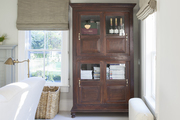 Large wood cabinet in bright beige living room.