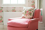 Floral wallpaper in a room with a pink armchair