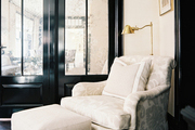 An upholstered roll-arm chair set against black lacquered doors and molding
