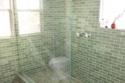 Farmhouse windows bring light into this green-tiled shower.