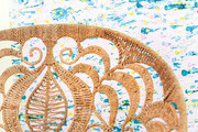 A detail of a rattan chair in front of blue, yellow, and white wallpaper.