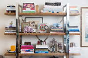 A wood and chrome bookshelf with books and global decor items