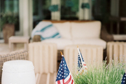 A white garden stool beside a planter filled with flags
