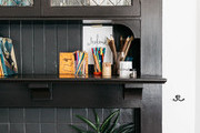 A black-tile fireplace with books.