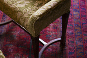 A velvet-upholstered stool on an oriental rug