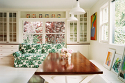 A floral-print green couch and an X-base table and bench in a dining space