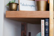 Plants, books and decor accents, including a coral catus from Costa Farms and an agate book end by West Elm, are layered on a cherry wood book shelf by Pink Sparrow Scenic