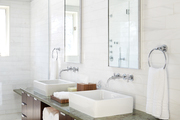 Contemporary bathroom with modern sinks on green counter top.