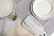 A table set with linen napkins, a jute table runner, stoneware dishes, and cheeseboard