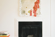 A white mirror, an orange side table, and a geometric rug surrounding a fireplace