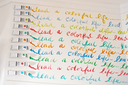 Paint tubes beside words printed on a wall