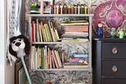 A shelf of books and toys against floral wallpaper