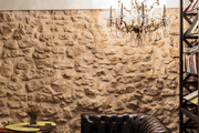 An inviting leather chesterfield in a stone-walled lounge