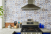 A kitchen with bold wall tiles that compliment the colorful storage cabinets.