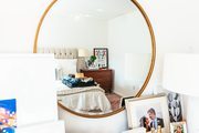 A round gilded mirror in a contemporary bedroom.