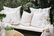 A mix of neutral pillows on an outdoor bench.