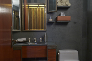 A bathroom with gray slate tile and wood detailing