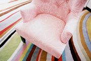 A pink armchair atop a multicolored rug