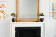 A gold-framed mirror hangs above a fireplace.
