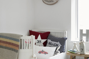 A nautical-themed kid's room with a white bed.