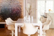 A simple white Parson's table surrounded by Eero Saarinen tulip arm chairs