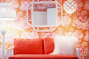 Pink-and-orange wallpaper and a leopard-print settee surrounded by white accents