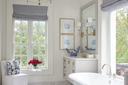 Blue and white ensuite bathroom with traditional tub and balcony.