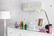 Colorful decor atop a mirrored white dresser in girls room.