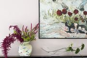 A floral arrangement on a living room mantel; above, a contemporary painting
