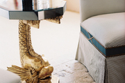A gold koi-fish-motif side table between a pair of striped slipper chairs