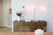 A wooden console table in a dining space below a pink neon sign.