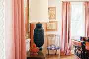 Pink curtains and upholstered chairs in a patterned-filled dining space