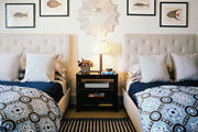 A pair of double beds atop a striped rug