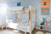 Bunk beds in a kid's bedroom with blue and white wallpaper.