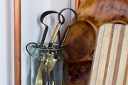 Kitchen tools and serving trays on a shelf with copper piping