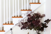 A console table next to a white stairway.